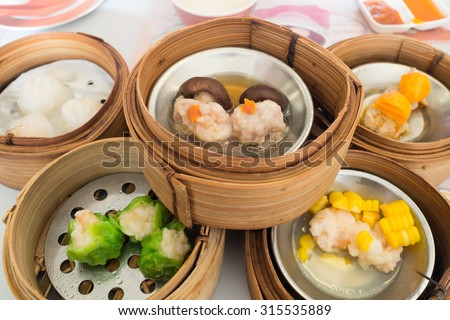 Yumcha, various chinese steamed dumpling in bamboo steamer in chinese restaurant. Dimsum in the steam basket, Chinese food - stock photo