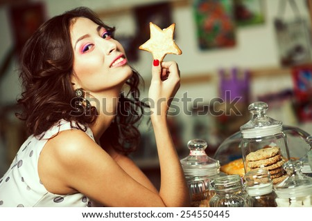 Yummy biscuits concept. Portrait of young brunette with arty make-up holding gingerbread posing with glass jars full of cookies in vintage cafe, restaurant. Retro style. Close up. Indoor shot - stock photo