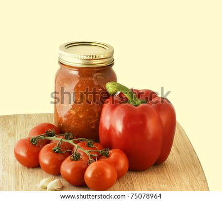 Yummy homemade spaghetti sauce preserve, tomatoes, red pepper and garlic on warm tone background.