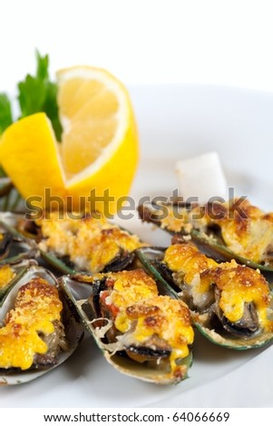 Yummy mussels under cheese and lemon - stock photo