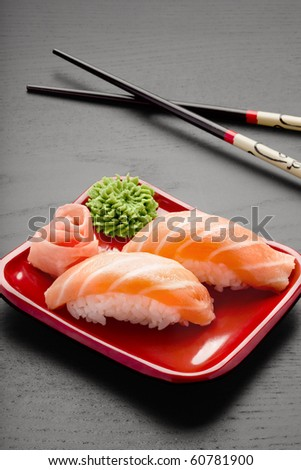 Yummy salmon. A close-up of chopsticks and a square plate with two pieces of salmon nigiri, wasabi and ginger. - stock photo