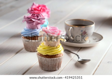 Yummy snack for sweet tooth. Fashionable cupcakes with interesting decoration on form of roses on the top. Vintage cup with tea and spoon near it. Cute wallpaper. - stock photo