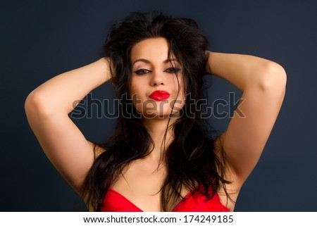 Yung beautiful brunette woman in beautiful red lingerie on dark background - stock photo