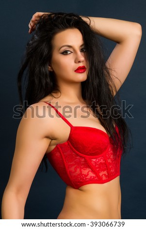 Yung beautiful brunette woman in beautiful red lingerie on dark background