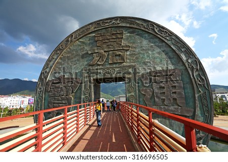 YUNNAN, CHINA - AUG 14: Tourists visit big symbol coin in through the bridge at town of Huize lies in the Northeast of Yunnan on August 14, 2010. The city has grown considerably over the past 20 years - stock photo