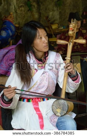 YUNNAN,CHINA - MAY 2015: A woman playing a horse head fiddle at a local village.