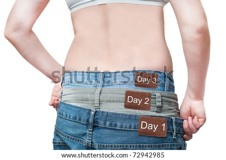 Yuong woman monitoring daily weight loss by wearing tree jeans. - stock photo