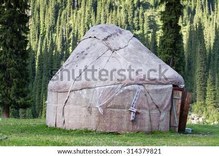 Yurt in Alatau Plateau, Tian Shan mountains near Karakol in Kyrgyzstan. Central Asia - stock photo