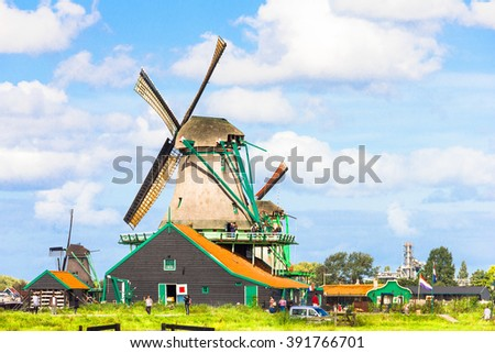 ZAANDAM, THE NETHERLANDS - SEPTEMBER 5, 2012: Tourists walking in the rural area in Zaandam. The city is famous for its windmills, museums and products, including cheeses and Dutch wooden clogs. - stock photo