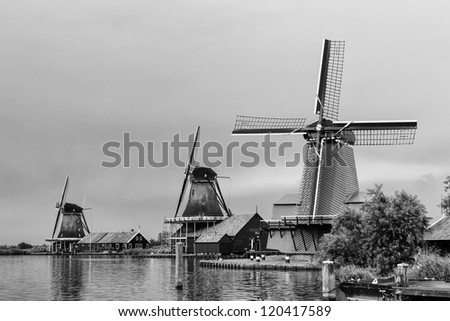 Zaanse Schans is a small village on the banks of the Zaan river, complete with tidy green houses and real working windmills. - stock photo