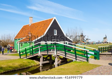 Zaanse schans, Netherlands - April 1, 2016: Zaanse Schans, North Holland, traditional village, tourists, green houses and windmills against blue cloudy sky