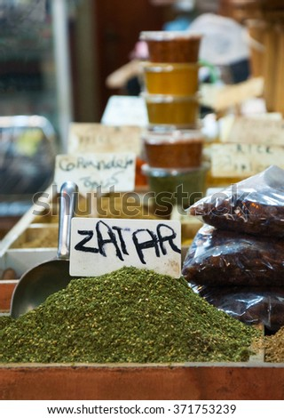 Zaatar and other spices for sale at the market in Old city of Jerusalem (Israel). Selective focus on product nameplate and on the zaatar spice under it. - stock photo