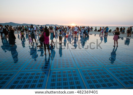 ZADAR, CROATIA - SEPTEMBER 1, 2016: People visit famous sea organ and watch sunset in Zadar, Croatia. The sea organ won European Prize for Urban Public Space award in 2006.