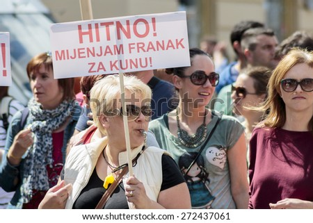 ZAGREB, CROATIA - APRIL 25, 2015: Woman carrying a banner during a protest against rising interest on loans in Swiss francs in Croatia, Zagreb  - stock photo