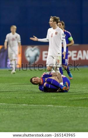 ZAGREB, CROATIA - MARCH 28, 2015: EURO 2016 qualifiers, group H - Croatia VS Norway. Mario MANDZUKIC (17) lying injured on the pitch.  - stock photo