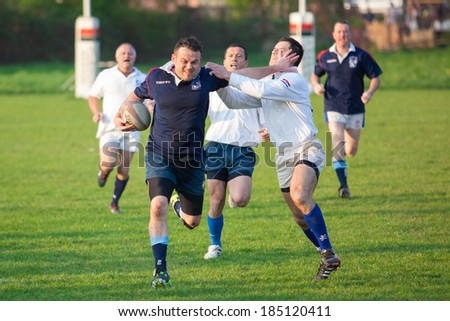 ZAGREB, CROATIA - MARCH 29, 2014: Friendly rugby match RC Zagreb Old Lions in white jersey (CRO) and Reigate RFC in blue jersey (UK). Unidentified players run for ball.