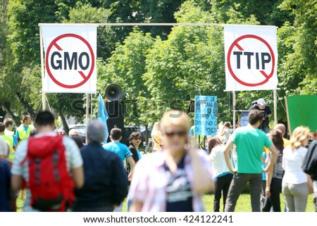 ZAGREB, CROATIA - MAY 21, 2016 :  Protesters march with signs raised through Zagreb in a protest against US biotechnology group Monsanto and against TTIP agreement.  - stock photo