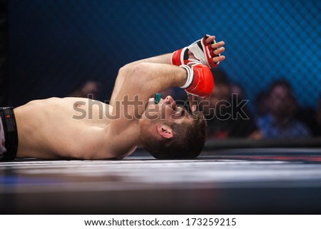 ZAGREB, CROATIA - NOVEMBER 2, 2013: Final fights at Croatian MMA legaue. Burhan AMETI (red gloves) on the floor after the match. - stock photo