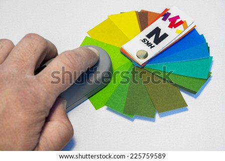 ZAGREB. CROATIA - OCTOBER 20, 2014: Hand holding pantone color cue measuring device on HKS catalog in printing house. HKS is a German reference catalog for mixing colors.
