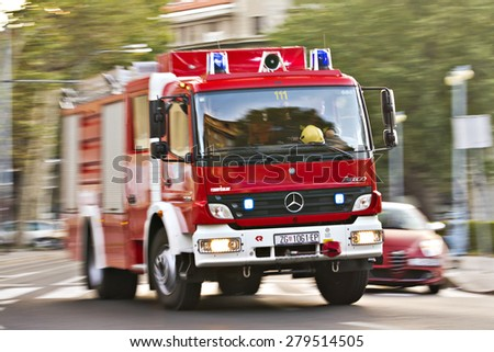 Zagreb, Croatia - September 10: Firefighters truck speeding to the scene under sirens and blue lights, cornering fast in the curve cutting out other cars in a rush on September 10, 2012 in Zagreb. - stock photo