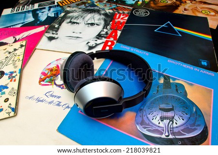 ZAGREB , CROATIA - SEPTEMBER 17 , 2014 -  Philips headphones on various old vinyl LP records on black background, product shot - stock photo