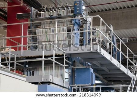 ZAGREB, CROATIA - SEPTEMBER 16, 2014: View of rotation Koenig Bauer machine in Printing house. Printing machine bends paper in full speed, paper is going through serious of rollers