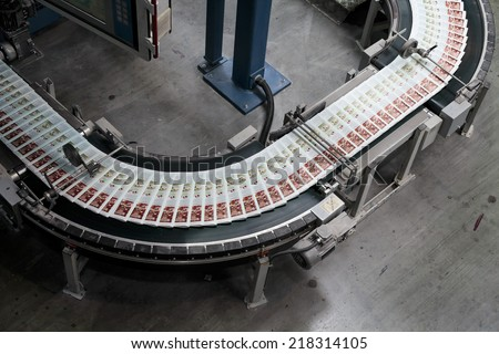 ZAGREB, CROATIA - SEPTEMBER 16, 2014: View of rotation Koenig Bauer machine in Printing house. Semi finished product going through the conveyor belt. - stock photo