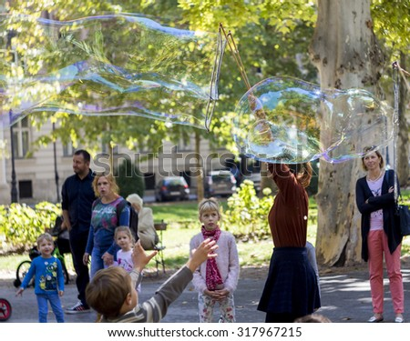 ZAGREB, CROATIA - SEPTEMBER 6, 2015: Woman blowing large bubbles in Zrinjevac park and entertaining kids and their parents