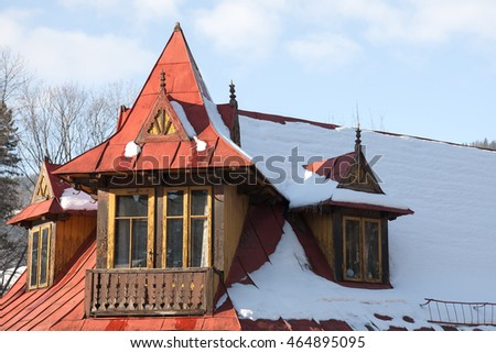 ZAKOPANE, POLAND - JANUARY 04, 2011: Painted in red sloping roof of the old dwelling house. Structural elements of the roof and the balcony is made in the style of architecture of the region