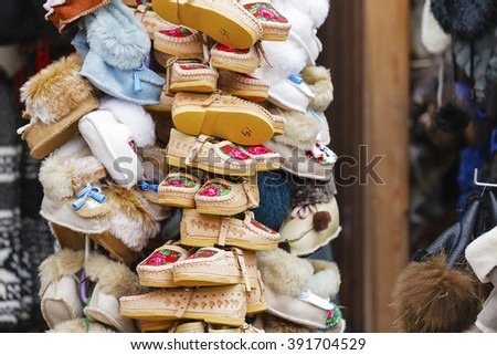 ZAKOPANE, POLAND - MARCH 11, 2016: Handmade footwear made of leather, decorated with the local traditional way put on sale at the local market. These shoes are also used as popular gifts from Zakopane - stock photo