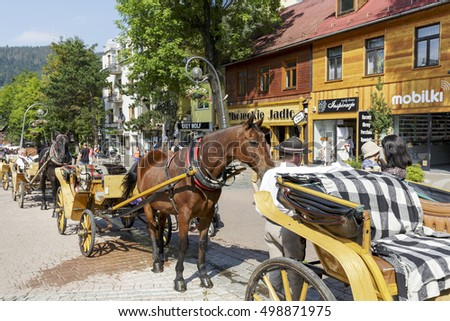 ZAKOPANE, POLAND - SEPTEMBER 12, 2016: Harnessed horses waits in line in the city on Krupowki street. The rides such carriages with sightseeing are a tourist attraction for many people coming to town