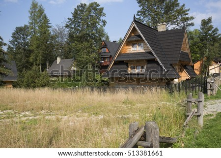 ZAKOPANE, POLAND - SEPTEMBER 12, 2016: Houses built in the style of mountain cottage can be seen behind the undeveloped meadow. These houses are surrounded by bushes and trees.