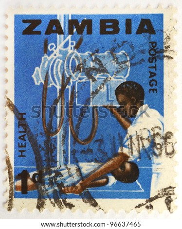 ZAMBIA - CIRCA 1970: a stamp from Zambia shows a doctor in the operating room with a young patient, circa 1970 - stock photo