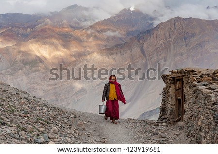 ZANSKAR PADUM, INDIA - MAY 12, 2016: Buddhist monk walking mountain village near monastery carrying bucket