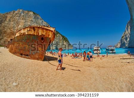 ZANTE ISLAND, GREECE - CIRCA JUNE 2015: Tourists in Navagio Bay with Pirate's Shipwreck - stock photo