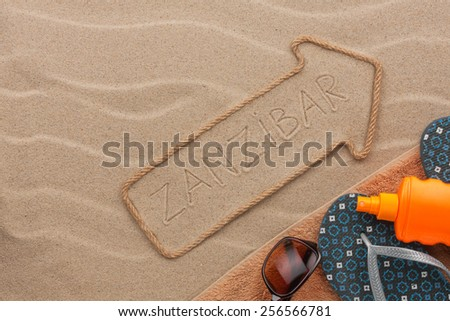 Zanzibar  pointer and beach accessories lying on the sand, as background