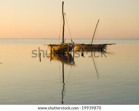 Zanzibar sunrise. Two Fishing boats on the Matemwe beach. One Dhow and one Ngalawa - stock photo