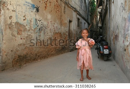 Zanzibar, Tanzania - February 16, 2008: Unknown smiling African girl with braids around 6 years old, standing near the old dilapidated, stone houses. - stock photo