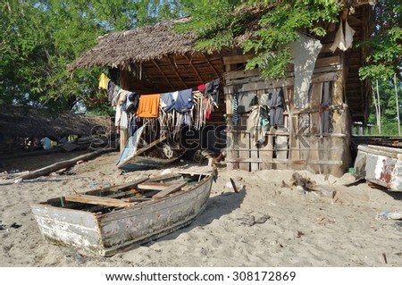 ZANZIBAR, TANZANIA -18 JUNE 2015- Local fishermen use the sandy beach behind the ruins of the Maruhubi Palace on the island of Zanzibar as an informal shipyard to build boats and fix their dhows. - stock photo