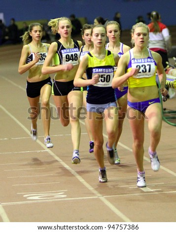 ZAPORIZHIA,UKRAINE - JAN 31: (L-R) Suroedova Irina, Nedashkivska Nina, Statkevich Inna run the 800 m. race on Ukrainian Junior Track and Field Championships on January 31, 2012 in Zaporizhia, Ukraine - stock photo