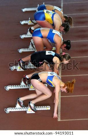 ZAPORIZHIA, UKRAINE - JAN.27: Unidentified girls on the start of the 60 meters dash on the Ukrainian Cup in Athletics on January 27, 2012 in Zaporizhia, Ukraine. - stock photo