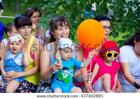 Zaporizhia/Ukraine- June 5, 2016: small children with mothers watching animation performance on charity family festival organized in regions with most quantity of refugees from Donetsk area
