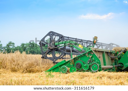 ZAPORIZHZHYA, UKRAINE - July 28, 2015: Close up Photo of John Deere Combine Harvester Harvesting Wheat. Summer Harvest Concept. - stock photo