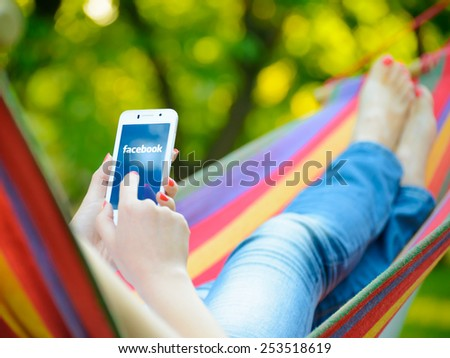 ZAPORIZHZHYA, UKRAINE - SEPTEMBER 20, 2014: Young Woman Using Facebook Application on her Smart Phone. - stock photo