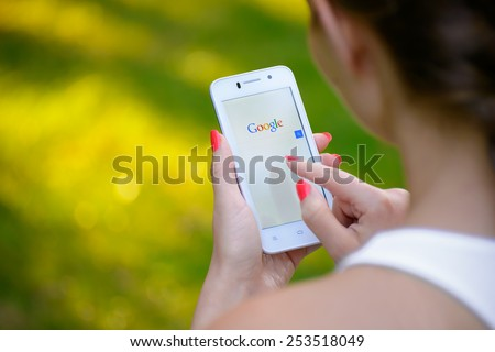 ZAPORIZHZHYA, UKRAINE - SEPTEMBER 20, 2014: Young Woman Using Google Web Search on her Smart Phone. - stock photo
