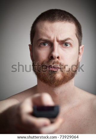 Zapping concept - annoyed man with tv remote control - stock photo
