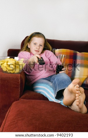 zapping TV, chips and cola - stock photo