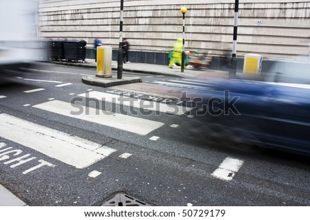 zebra crossing or pedestrian crossing in london with motion blur of traffic - stock photo