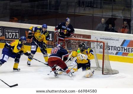 ZELL AM SEE, AUSTRIA - DECEMBER 7: Austrian National League. Big save by Goalie Bartholomaeus. Game EK Zell am See vs. Red Bulls Salzburg (Result 4-6) on December 7, 2010 at hockey rink of Zell am See, Austria - stock photo