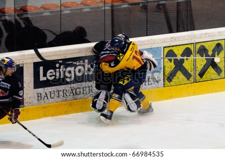 ZELL AM SEE, AUSTRIA - DECEMBER 7: Austrian National League. Putnik charging Goalie Konovalov. Game EK Zell am See vs. Red Bulls Salzburg (Result 4-6) on December 7, 2010 at hockey rink of Zell am See, Austria